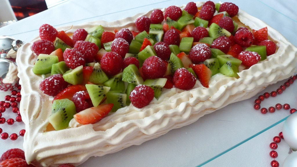 A rectangular Holiday Pavlova filled with cream and fresh strawberries, raspberries and kiwi fruit.