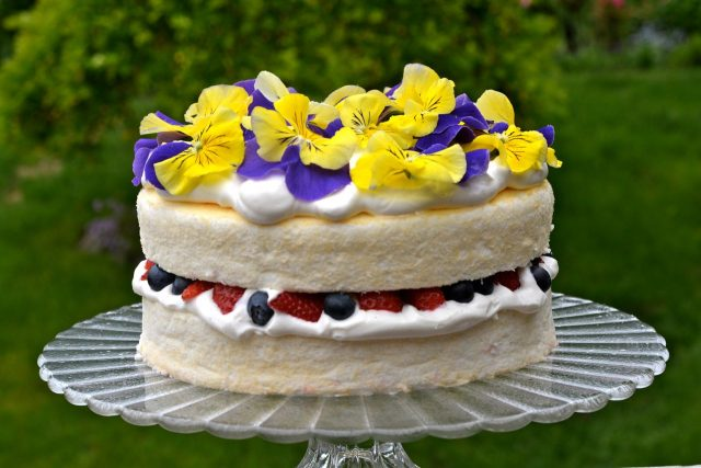 A pedestal tray with a gluten free Angel Food Cake filled with whipped cream and fresh berries, garnished with pansies.