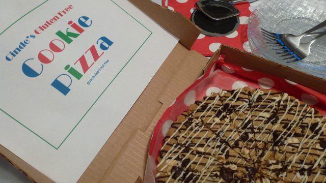 A pizza box with a gluten free Chocolate Chip Cookie Pizza.