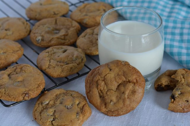 A baking rack of gluten free Chocolate Chip Cookies and a glass of milk.