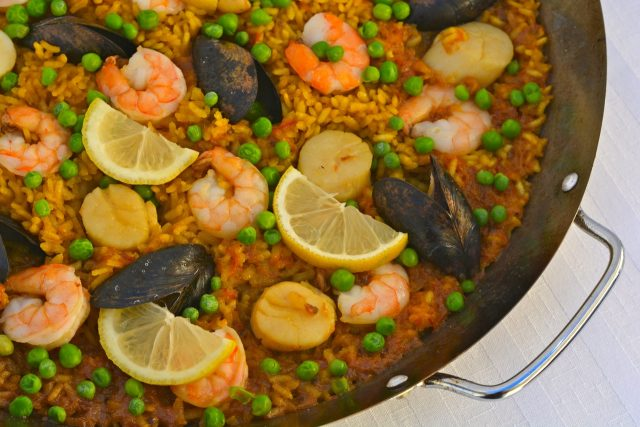 A paella pan filled with Paella with Seafood