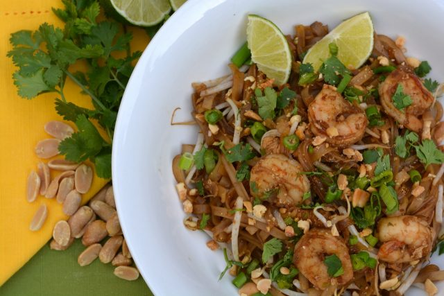 Shrimp Pad Thai topped with cilantro, chopped peanuts and lime wedges.