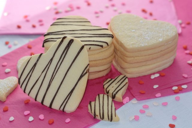 A stack of Gluten Free Sugar Cookies drizzled with chocolate.