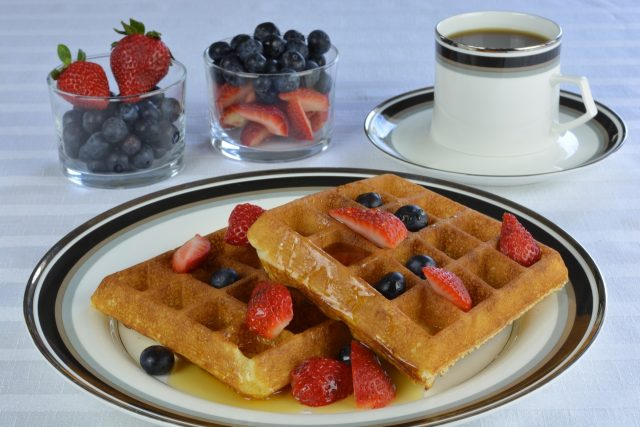 Gluten Free Waffles with strawberries, blueberries and maple syrup.
