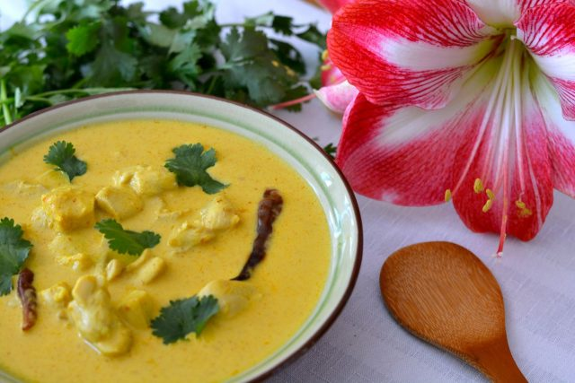 A bowl of Thai Yellow Chicken Curry garnished with fresh cilantro.