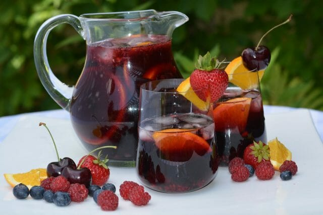 Two glasses and a pitcher of Prosecco Berry Sangria.