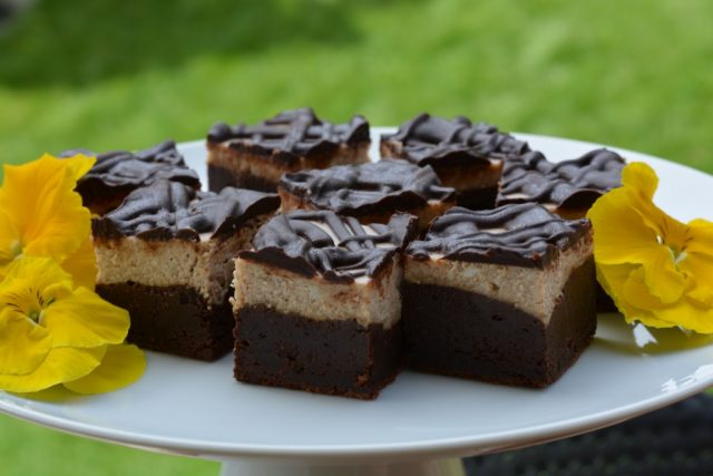 A pedestal tray with gluten free Mochaccino Cheesecake Brownies decorated with pansies.