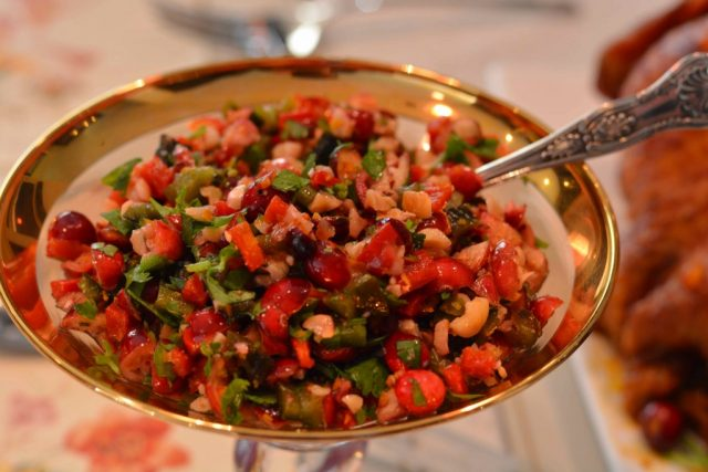 A gold rimmed dish of cranberry orange and cilantro salsa bursting with flavour from citrus zest.