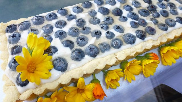 A gluten free flaky pie crust filled with vanilla cream and topped with blueberries.