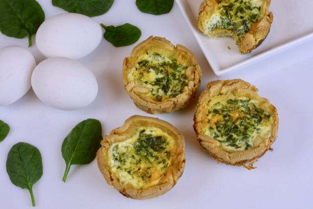 Three individual quiches made with spinach and feta.