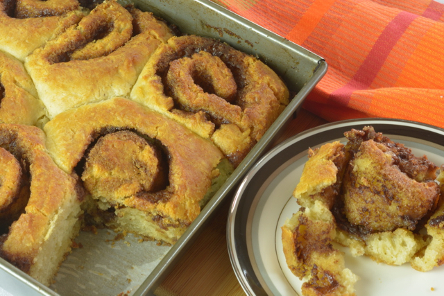 A pan of biscuit cinnamon rolls with one on a plate beside it.