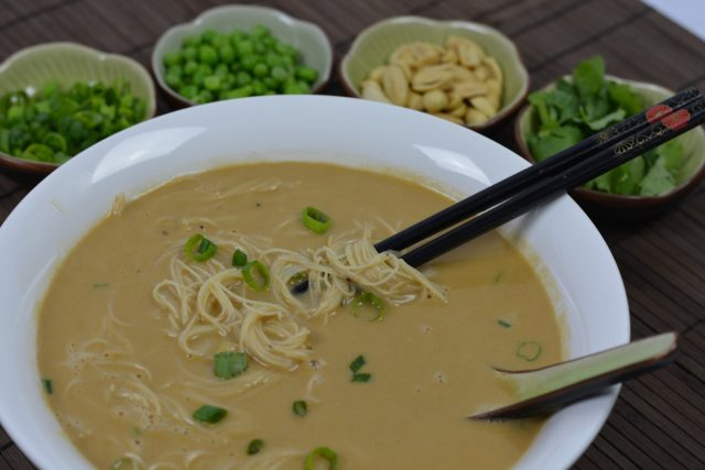 A bowl of Noodle Soup with Peanut Sauce surrounded by optional toppings.