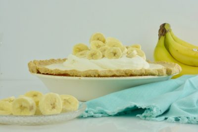 Banana Cream Pie covered in whipped cream and sliced bananas.