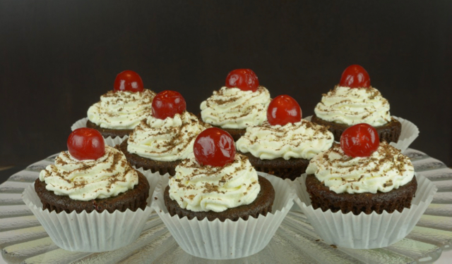 A tray of Black Forest Cupcakes topped with maraschino cherries