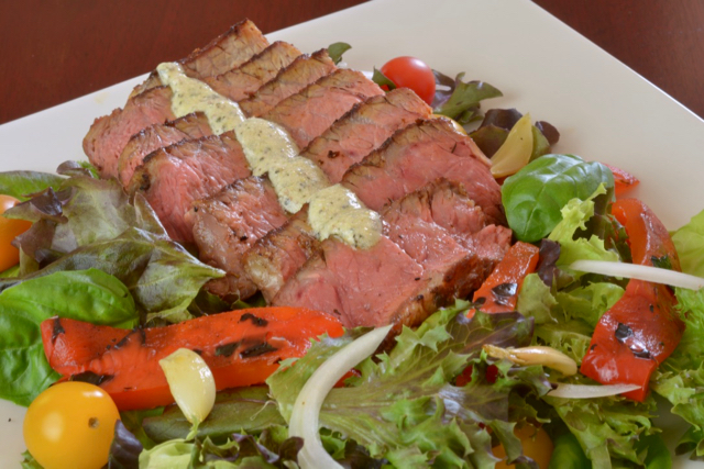 A plate of Blackened Steak Salad with peppers, tomato, onion and blue cheese dressing.