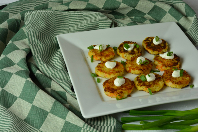 Bubble and Squeak Patties topped with sour cream and chopped green onions.