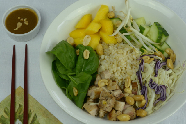 A big white bowl filled with brown rice, raw spinach and cabbage, mango and peanuts.