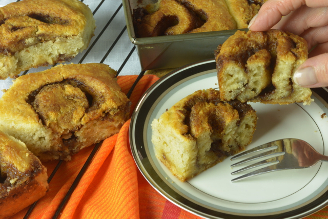 A biscuit cinnamon roll on a plate cut in half, surrounded by other cinnamon rolls in and out of the baking pan.