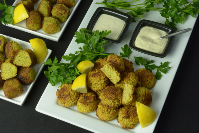 A platter of Falafel Balls with Tahini Sauce garnished with fresh parsley and lemon wedges.