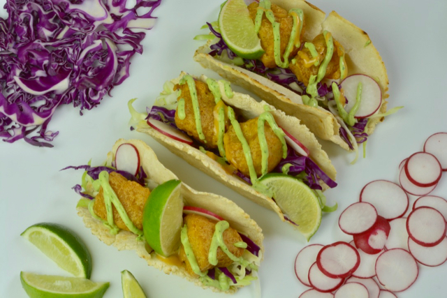 Fish tacos with avocado crema and lime surrounded by shredded purple cabbage and sliced radishes.