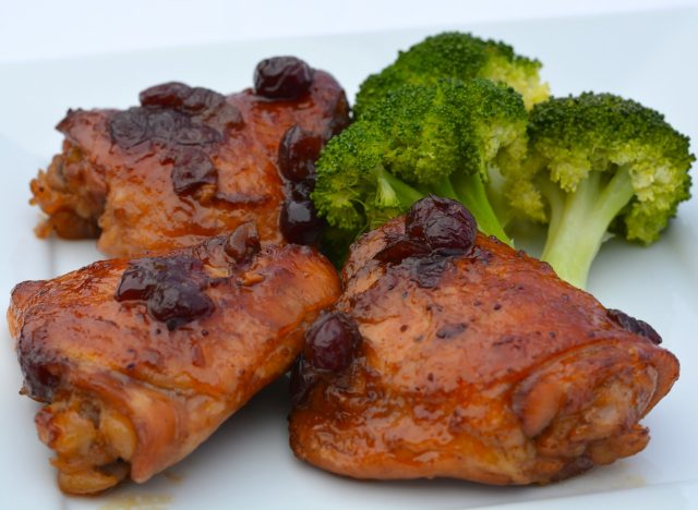 A plate of Cranberry Orange Chicken with broccoli on the side.