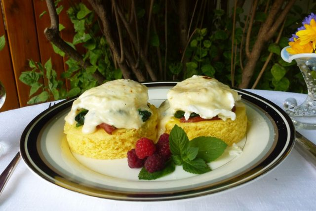 A white plate with gluten free cornbread rounds topped with ham, spinach, eggs and Mornay sauce, Eggs Florentine.