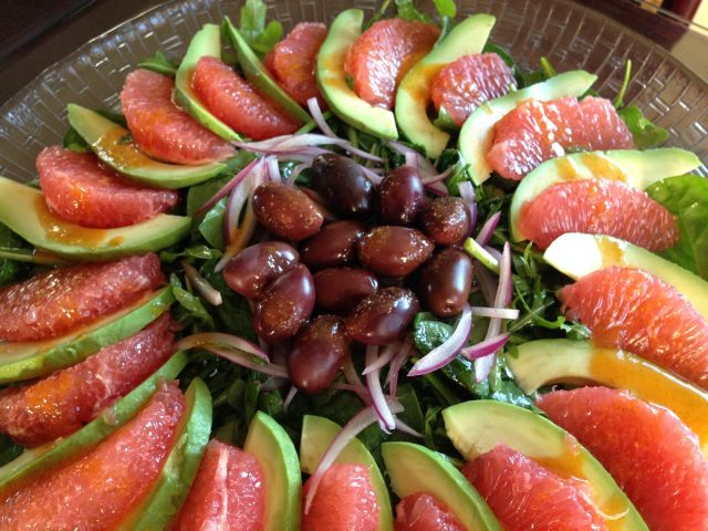 A platter of gluten free Grapefruit and Avocado Salad with Tomato Cumin Dressing on a bed of arugula with red onion slivers.