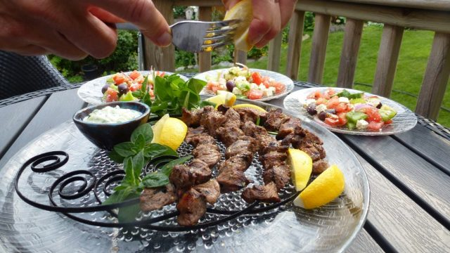 gluten free grilled lamb souvlaki on circular skewers with lemon.