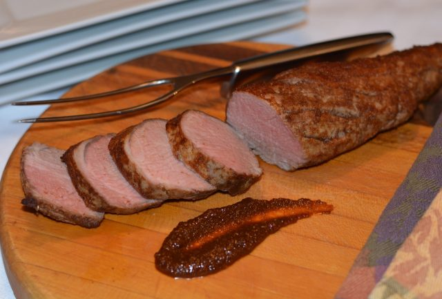 A cutting board with slices of a Pork Tenderloin with Asian Flavours.