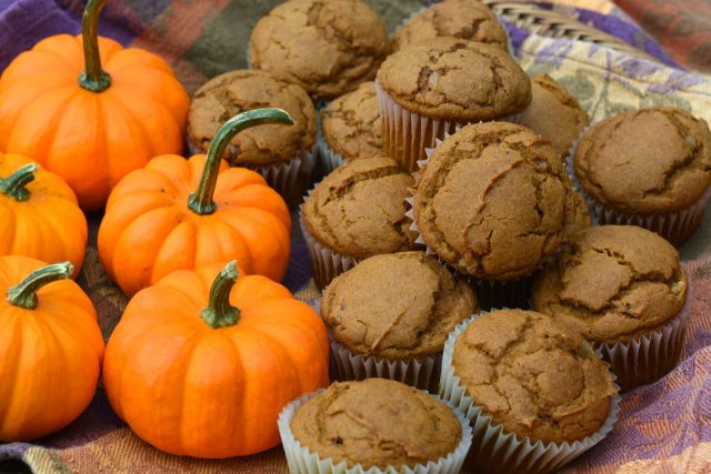 A basket of Gluten Free Pumpkin Ginger Muffins beside orange mini pumpkins