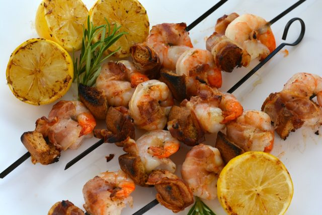 A platter with skewers of Gluten Free Shrimp on the Barbie.
