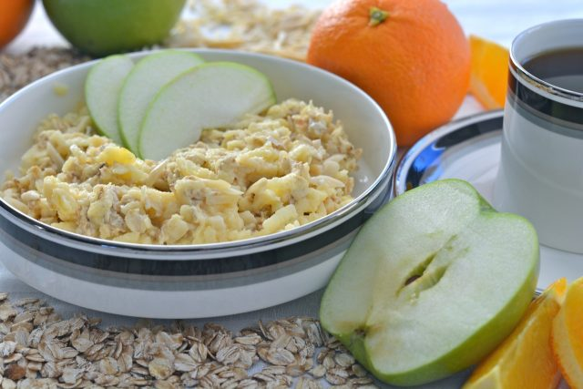 A bowl of Swiss muesli with grated apple and almonds.