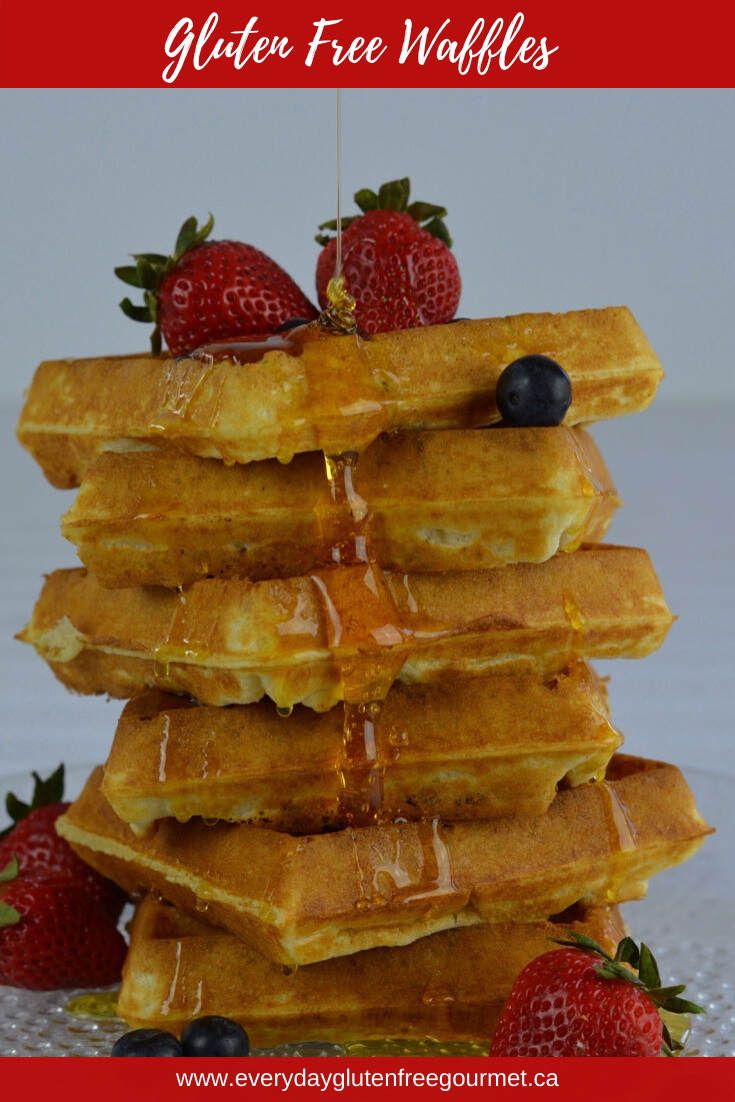 A pile of Gluten Free Waffles with strawberries and blueberries, and corn syrup drizzling all the way down.