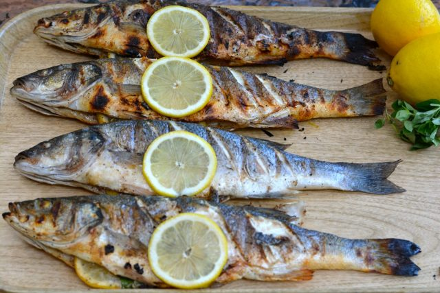 Whole Grilled Branzino right off the barbecue garnished with lemon slices.