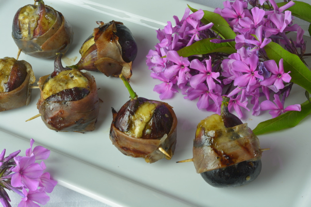Grilled Figs Stuffed with Blue Cheese and wrapped with prosciutto on a white platter surrounded by pink flowers