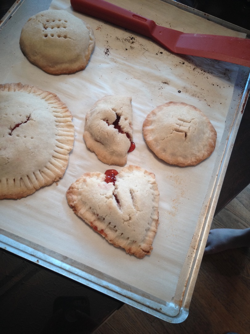 A heart shaped Cherry Hand Pie and some rounds ones on a baking sheet