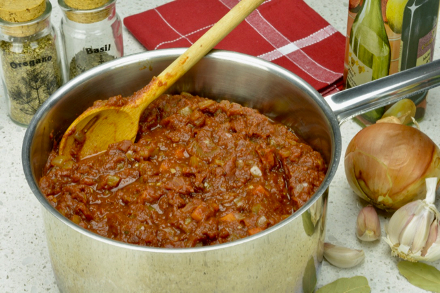 A pot of Homemade Tomato Sauce surrounded by some of the ingredients.