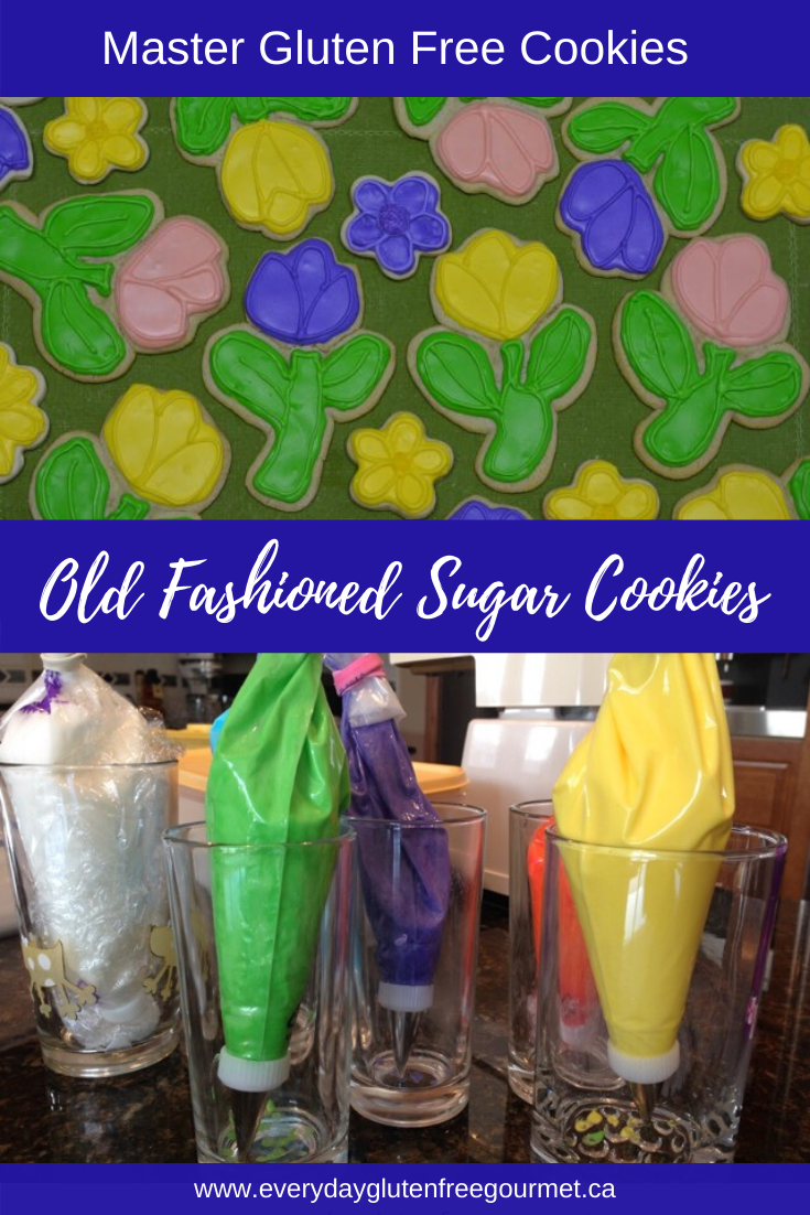 Old Fashioned Sugar Cookies in flower shapes decorated with royal icing in yellow, pink and purple.