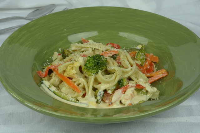A plate of gluten free Pasta Primavera sprinkled with freshly grated Parmesan cheese.