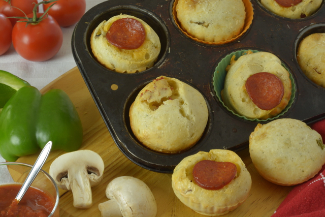 Pepperoni Pizza Cheese Buns in the pan surrounded by green pepper, mushrooms and pizza dipping sauce.