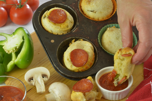 A tray of Pepperoni Pizza Cheese Buns and someone dipping theirs into the pizza dipping sauce.