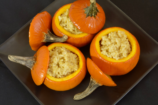 Top down view of sugar pumpkins filled with pumpkin risotto served on a black plate.
