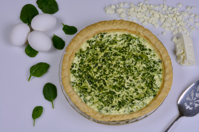 A Spinach Feta Quiche ready to be cut and served.
