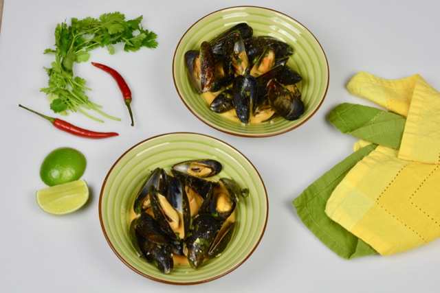 An appetizer of Thai Coconut Mussels with red curry paste and cilantro