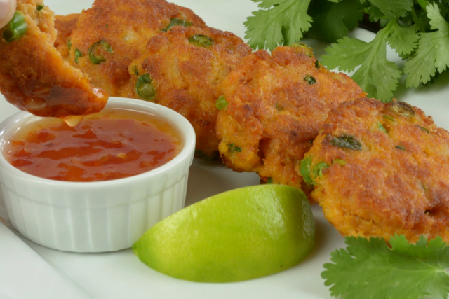A platter of Thai Fish Cakes and someone dipping one into the sweet chile sauce.