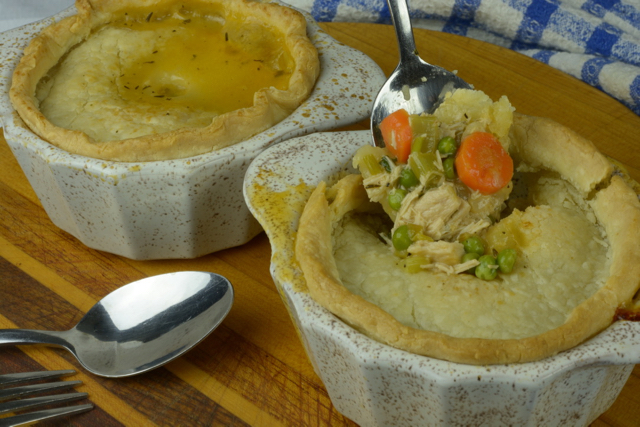 A spoon dug into a Turkey Pot Pie showing the filling.