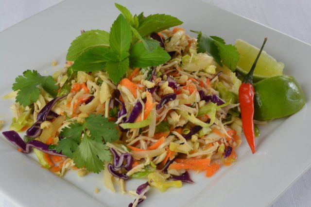 Vietnamese Cabbage Chicken Salad garnished with peanuts, mint and cilantro.