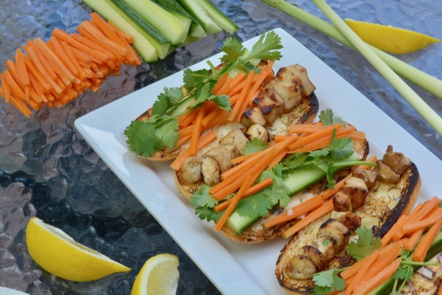 Two assembled Vietnamese Subs with Lemongrass Chicken, carrot, cucumber and cilantro