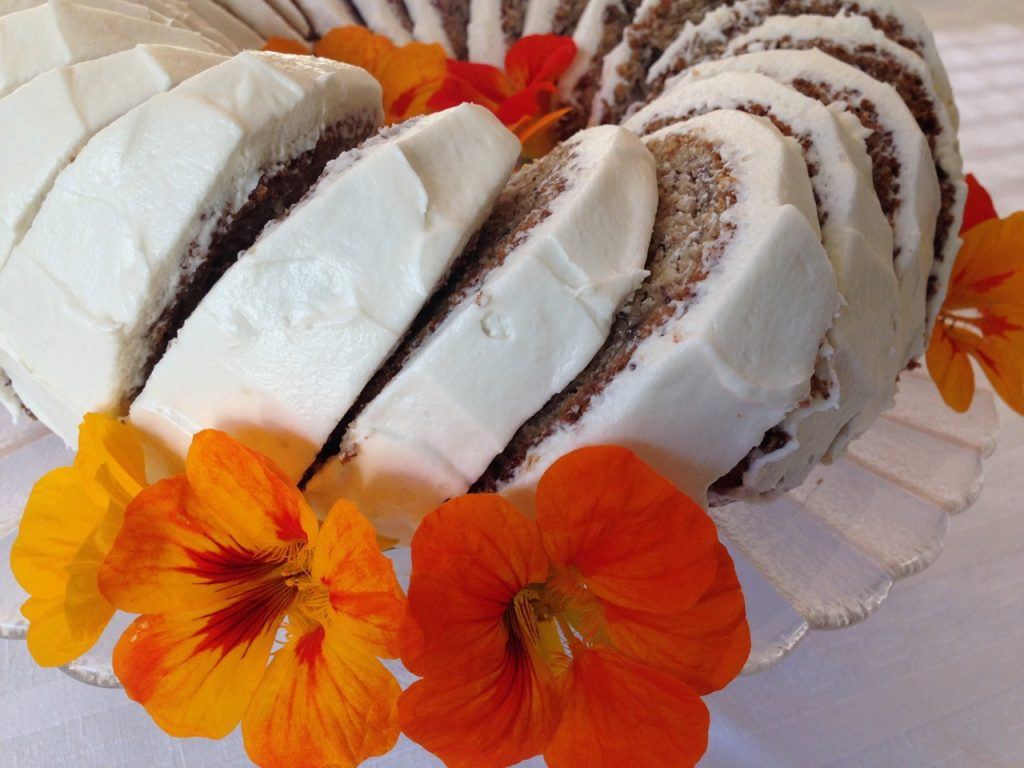 Slices of Banana Bundt Cake with Cream Cheese Icing garnished with fresh nasturtiums.