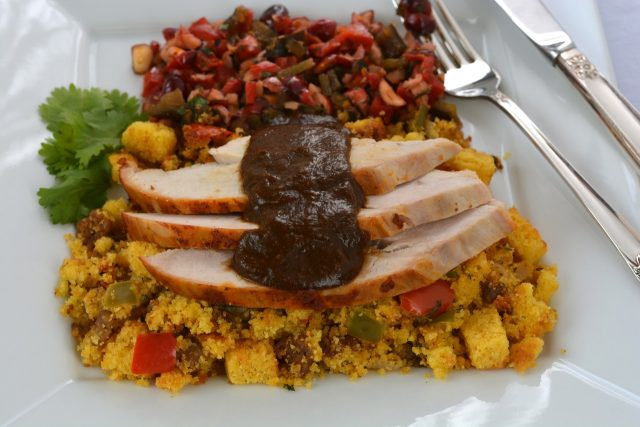 A plate of gluten free Cornbread Chorizo Stuffing topped with turkey slices.